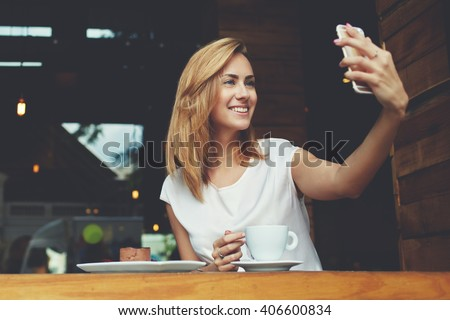 Happy smiling hipster girl making self portrait with mobile phone camera while sitting in modern coffee shop, cheerful woman posing while photographing herself for social network picture, copy space #406600834