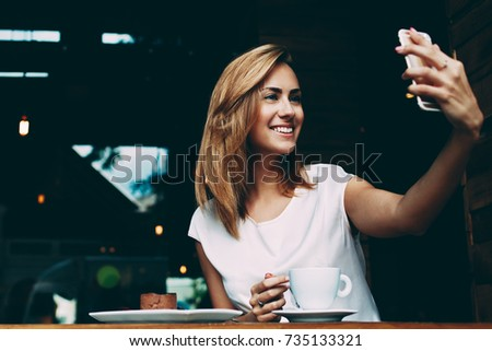Happy smiling hipster girl making self portrait with mobile phone camera while sitting in modern coffee shop, cheerful woman posing while photographing herself for social network picture, copy space #735133321