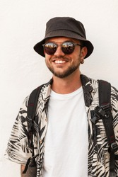 Happy smiling hipster man with smile in fashion summer clothes with sunglasses and hat stands near white wall