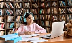 Happy smiling indian junior student wearing headphones having online virtual learning language class on laptop. Cute latin schoolgirl writing in workbook watching video meeting with teacher.