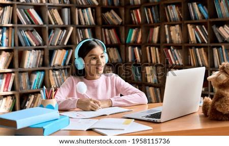 Happy smiling indian junior student wearing headphones having online virtual learning language class on laptop. Cute latin schoolgirl writing in workbook watching video meeting with teacher. Stock photo ©