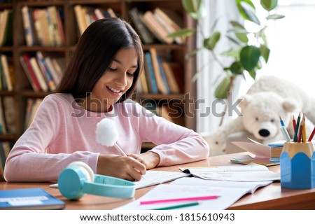 Happy smiling indian latin preteen school girl pupil studying at home sitting at desk. Smart cute hispanic kid primary school student writing in exercise book doing homework, learning at table.
