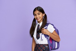 Happy smiling indian preteen girl, latin kid schoolgirl with ponytails wears uniform holding backpack standing isolated on lilac violet background looking at camera, back to school concept, portrait.