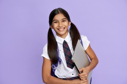 Happy smiling indian preteen girl, latin kid wears school uniform holding backpack and laptop computer isolated on lilac violet background looking at camera, remote learning online concept, portrait.