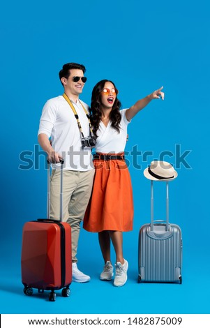 Happy smiling interracial tourist couple with baggage enjoying their summer vacation getaway together in blue studio background