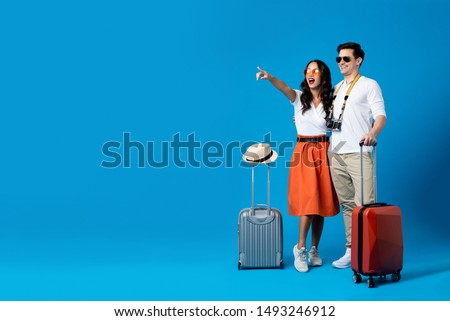 Happy smiling interracial tourist couple with luggage enjoying their summer vacation getaway together in blue studio background