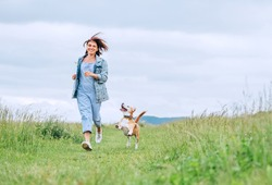 Happy smiling jogging female with fluttering hairs and her beagle dog running and looking at eyes. Walking by meadow grass path in nature with pets, healthy active people lifestyle concept image.