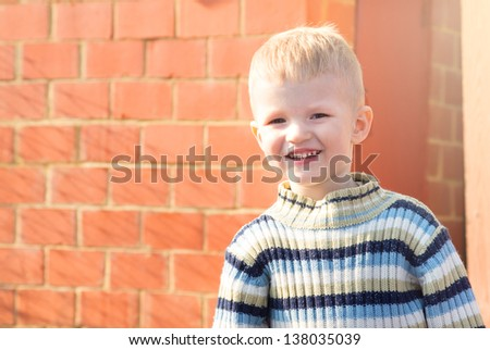 Happy smiling joyful caucasian child (little boy) standing near red brick wall, lose up portrait, copy space.