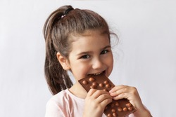 Happy smiling kid girl biting tasty chocolate with empty copy space. Isolated portrait