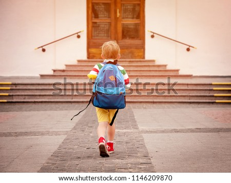 Happy smiling kid in glasses is going to school for the first time. Child boy with bag go to elementary school. Child of primary school. Pupil go study with backpack. Back to school #1146209870