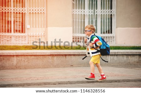Happy smiling kid in glasses is going to school for the first time. Child boy with bag go to elementary school. Child of primary school. Pupil go study with backpack. Back to school