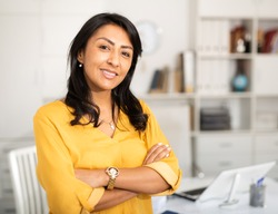 Happy smiling Latin American businesswoman standing in office with arms crossed looking at camera