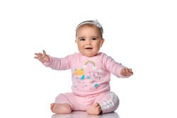 Happy smiling laughing barefoot baby in tracksuit and headband with bow sits on the floor with arms outstretched wide. Happy infancy and childhood concept