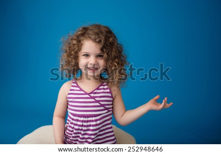 Happy smiling laughing child looking at camera: girl with curly hair holding something or pointing at something