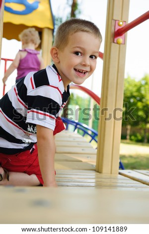 Happy smiling little blond boy at playground