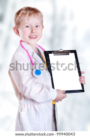 Happy smiling little boy in doctor uniform with medical tools