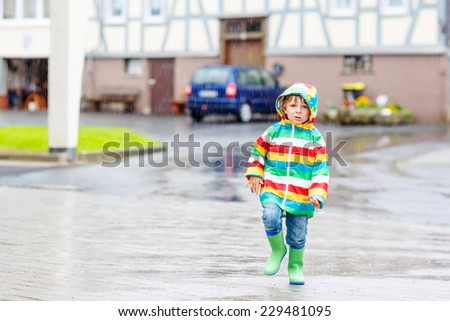 Happy smiling little boy walking in city through rain, wearing colorful rain coat and green boots outdoors at rainy day. Having fun.
