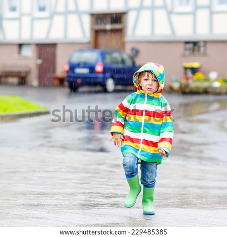 Happy smiling little boy walking in city through rain, wearing colorful rain coat and green boots outdoors at rainy day. Having fun. Square format.