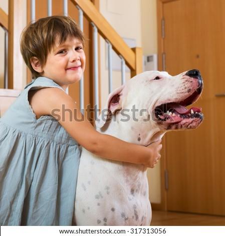 Happy smiling little girl hugging big white dog at home