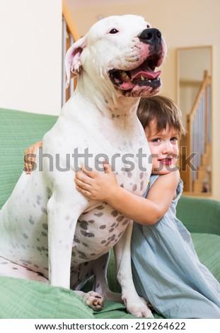 Happy smiling little girl hugging big white dog at home. Focus on girl