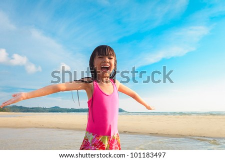 Happy smiling little girl on beach