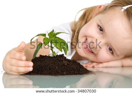 Happy smiling little girl protecting a plant - isolated