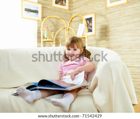 happy smiling little girl sitting on the sofa and reading a book