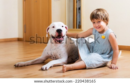 Happy smiling little girl with big white dog on the floor at home