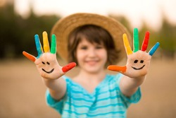 Happy smiling little girl with hands in painted in funny face play outdoor in summer park. Focus on hands
