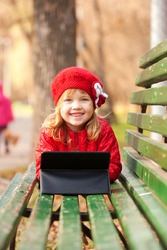 Happy smiling little girl working with tablet pc and lying on bench in the park.