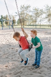 Happy smiling little preschool boys friends swinging on swings at playground outside on summer day. Happy childhood lifestyle concept. Seasonal outdoor activity for kids.