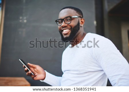 Happy smiling male blogger holding smartphone gadget in hand indoors and feeling good on leisure, portrait of cheerful hipster guy in eyewear with mobile phone spending time on publicity area