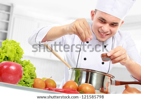 happy smiling male chef cooking in the kitchen