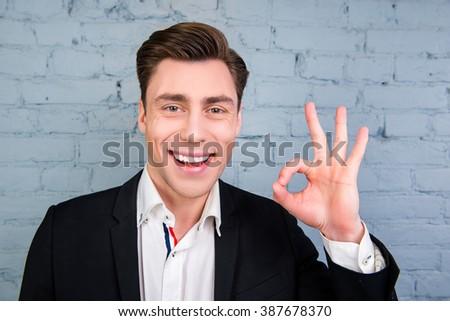 """Happy smiling man in black jacket gesturing """"OK"""" #387678370"""