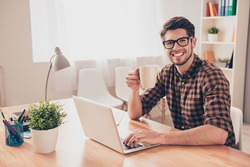 Happy smiling man in glasses working with laptop and drinking coffee