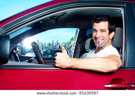 Happy smiling man in new car. Driving.