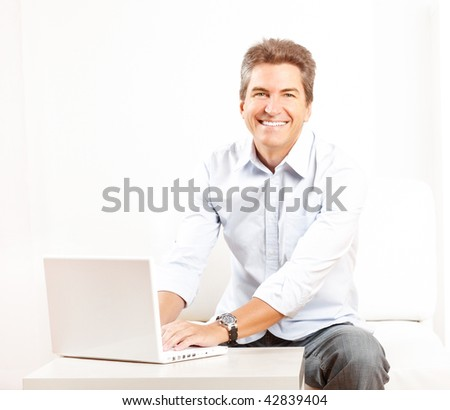 Happy smiling man with laptop at home