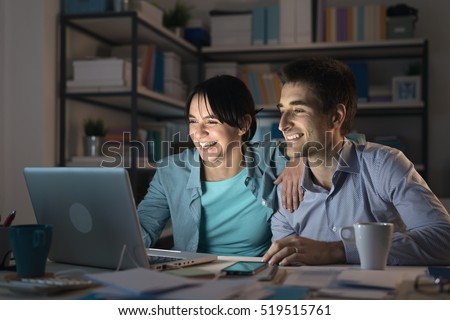 Happy smiling married couple at home using a laptop, connecting to internet and networking, communication and internet concept stock photo