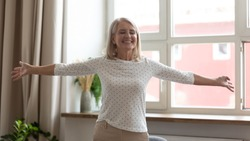 Happy smiling mature woman standing with arms outstretched at home, thankful satisfied older female with closed eyes enjoying life, having fun, rejoicing success, weekend or retirement