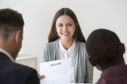Happy smiling millennial applicant being interviewed by diverse hr managers, recruiting team reading resume of positive funny graduate girl looking for first job, good impression and hiring concept