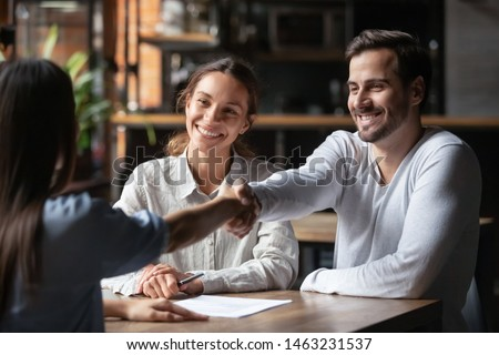 Happy smiling millennial couple handshake get acquainted with female real estate agent meeting together in cafe, excited husband and wife shake hand of broker or banker thanking for help