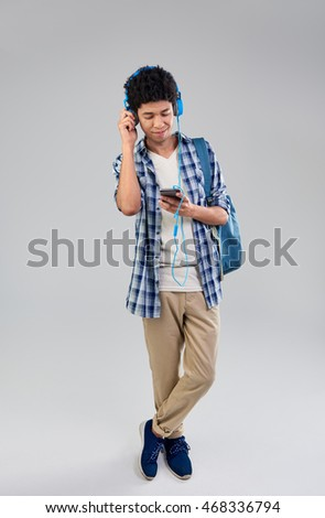 Happy smiling mixed race man choosing a song playlist on his mobile cell phone #468336794