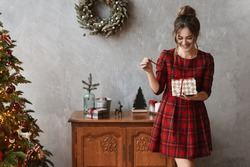 Happy smiling model girl in plaid red dress holding the present box and posing near Christmas tree. Young beautiful woman unpacking Christmas gift in the interior decorated for New year.