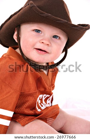 happy smiling 6-month old baby boy portrait wearing cowboy hat and shirt reads Texas