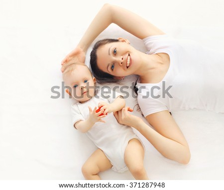 Happy smiling mother and baby lying on bed at home, top view