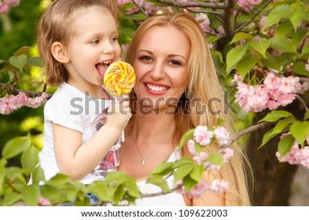 happy smiling mother with little daughter licks candy spring park outdoor