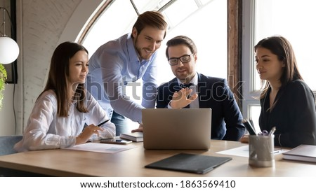 Happy smiling multiethnic group of young employees interns students learn to solve business problems on training course with professional expert coach mentor tutor assistance using modern computer app Foto stock ©