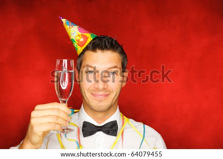 Happy smiling new years eve celebrating man with hat on party
