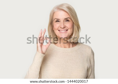 Happy smiling old lady showing ok sign headshot at studio. Elderly woman giving good advice, offer, help portrait isolated on grey background. Customer and client, sale, discount, business concept #1444020017