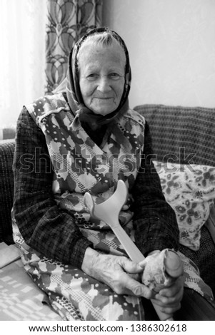 Happy, Smiling Old woman, Grandmother, Senior is sitting on the couch in the cozy home. Middle european culture. Wearing traditional costume,  slovak, middle european costume, clothes. Retro, vintage
